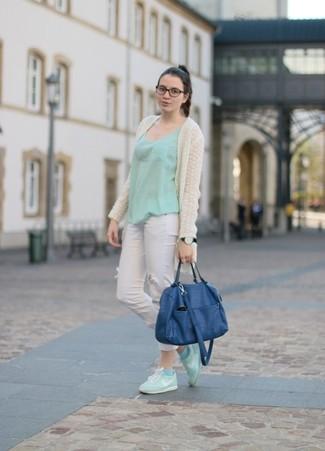 Entscheiden Sie sich für Komfort in einer hellbeige Strick Strickjacke mit einer offenen Front und weißen engen Jeans mit Destroyed-Effekten. Weiße und grüne niedrige Sneakers sind eine kluge Wahl, um dieses Outfit zu vervollständigen.