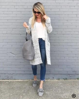 Wie kombinieren: weiße Strick Strickjacke mit einer offenen Front, weißes Trägershirt, blaue enge Jeans, graue Wildleder Slipper