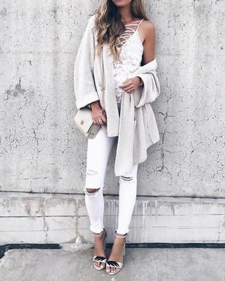 Wie kombinieren: hellbeige Strick Strickjacke mit einer offenen Front, weißes Spitze Trägershirt, weiße enge Jeans mit Destroyed-Effekten, weiße Leder Sandaletten