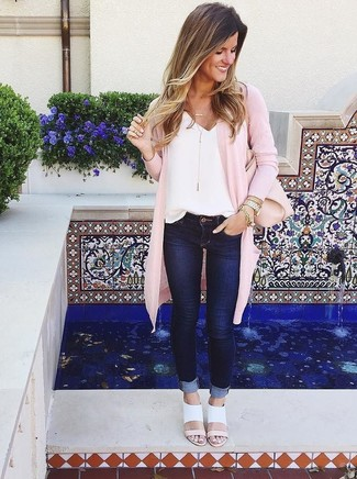 Wie kombinieren: rosa Strickjacke mit einer offenen Front, weißes Seide Trägershirt, dunkelblaue enge Jeans, weiße Leder Sandaletten