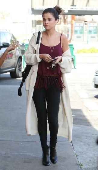 Wie kombinieren: hellbeige Strick Strickjacke mit einer offenen Front, dunkelrotes Trägershirt mit Fransen, schwarze enge Jeans, schwarze Leder Stiefeletten