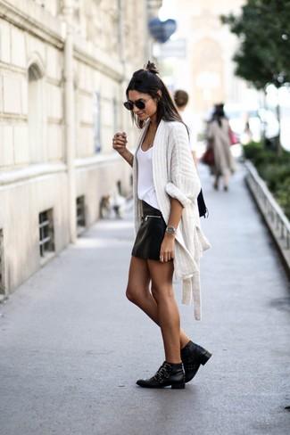 Wie kombinieren: weiße Strick Strickjacke mit einer offenen Front, weißes Trägershirt, schwarzer Leder Minirock, schwarze beschlagene Leder Stiefeletten