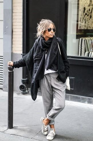 Eine schwarze Strick Strickjacke mit einer offenen Front und eine graue Chinohose sind das Outfit Ihrer Wahl für faule Tage. Ergänzen Sie Ihr Look mit grauen Segeltuch niedrigen Sneakers.