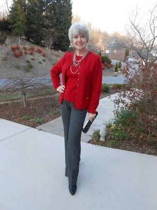 Wie kombinieren: rote Strickjacke, roter Pullover mit einem Rundhalsausschnitt, dunkelgraue Anzughose, schwarze Leder Stiefeletten