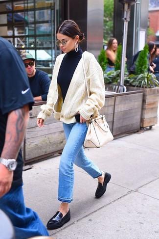 Wie kombinieren: hellbeige Strick Strickjacke, dunkelblauer Rollkragenpullover, hellblaue Jeans, schwarze Leder Slipper