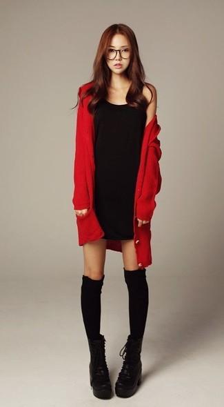 Wie kombinieren: rote Strickjacke, schwarzes Trägerkleid, schwarze klobige Schnürstiefeletten aus Leder, schwarze hohe Socken