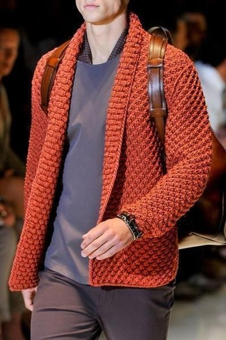 Wie kombinieren: orange Strick Strickjacke, graues T-Shirt mit einem Rundhalsausschnitt, dunkelbraune Chinohose, brauner Leder Rucksack