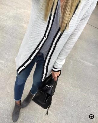 Wie kombinieren: weiße und schwarze Strick Strickjacke, graues T-Shirt mit einem V-Ausschnitt, dunkelblaue enge Jeans, dunkelgraue Wildleder Stiefeletten