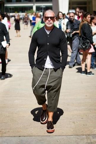Nick Wooster trägt Schwarze Strickjacke, Weißes T-Shirt mit Rundhalsausschnitt, Olivgrüne Jogginghose, Dunkelbraune Leder Derby Schuhe
