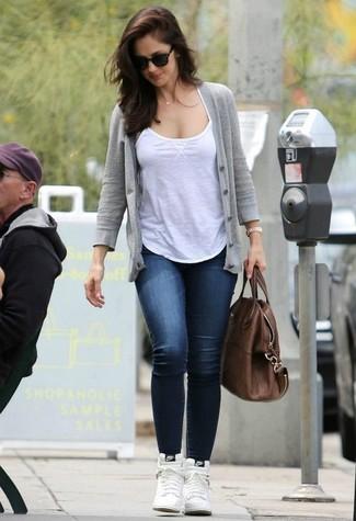Wie kombinieren: graue Strickjacke, weißes Trägershirt, dunkelblaue enge Jeans, weiße hohe Sneakers aus Leder