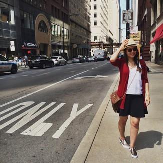 Wie kombinieren: rote Strickjacke, weißes Trägershirt mit Lochstickerei, schwarzer Skaterrock, goldene Slip-On Sneakers
