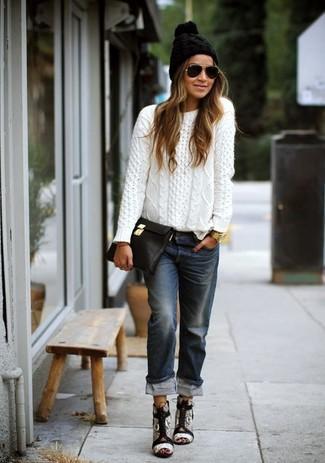 Wie kombinieren: weißer Strickpullover, dunkelblaue Boyfriend Jeans, graue Leder Sandaletten mit Schlangenmuster, schwarze Leder Clutch