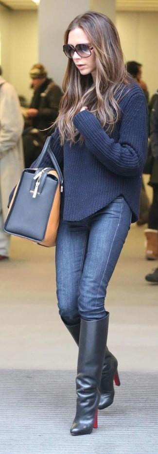 Wie kombinieren: dunkelblauer Strickpullover, dunkelblaue enge Jeans, schwarze kniehohe Stiefel aus Leder, beige Leder Reisetasche