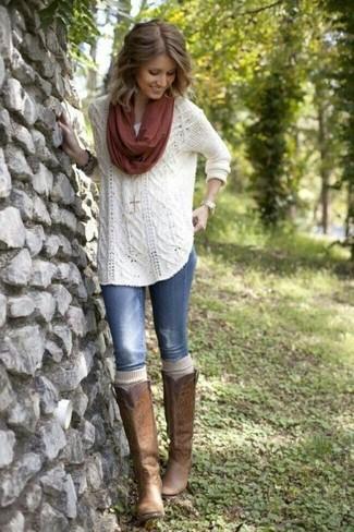 Wie kombinieren: weißer Strickpullover, blaue enge Jeans mit Destroyed-Effekten, braune kniehohe Stiefel aus Leder, dunkelroter Schal