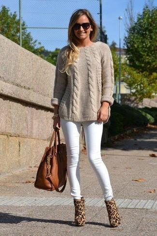Wie kombinieren: hellbeige Strickpullover, weiße enge Jeans, beige Stiefeletten aus Kalb Haar mit Leopardenmuster, braune Shopper Tasche aus Leder