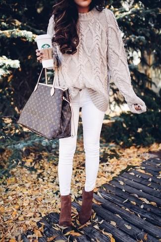 Wie kombinieren: hellbeige Strickpullover, weiße enge Jeans, braune Wildleder Stiefeletten, dunkelbraune bedruckte Shopper Tasche aus Leder
