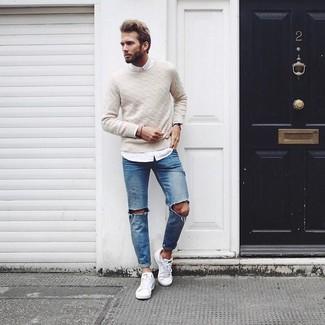Wie kombinieren: hellbeige Strickpullover, weißes Langarmhemd, blaue Jeans mit Destroyed-Effekten, weiße niedrige Sneakers