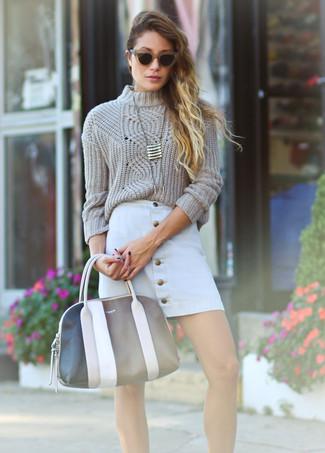 Wie kombinieren: hellbeige Strickpullover, weißer Rock mit Knöpfen, schwarze und weiße Shopper Tasche aus Leder, goldener Anhänger