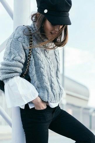 Wie kombinieren: grauer Strick Strickpullover, weiße Langarmbluse mit Rüschen, schwarze enge Jeans, schwarze Wildleder Umhängetasche