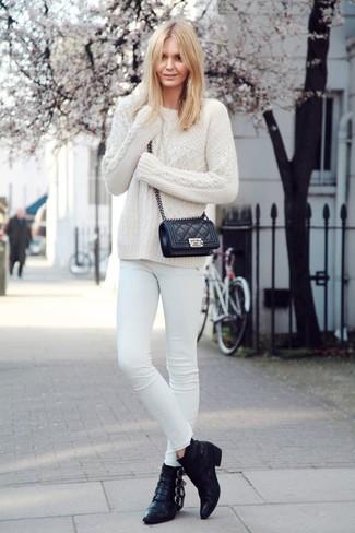 Wie kombinieren: weißer Strickpullover, weiße enge Jeans, schwarze Leder Stiefeletten, schwarze gesteppte Leder Umhängetasche