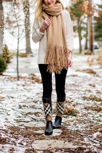 Wie kombinieren: weißer Strickpullover, schwarze Leggings, schwarze Gummistiefel mit Schottenmuster, beige Schal