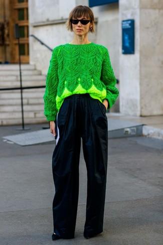 Wie kombinieren: grüner Strickpullover, dunkelblaue weite Hose, schwarze Wildleder Pumps, schwarze Sonnenbrille