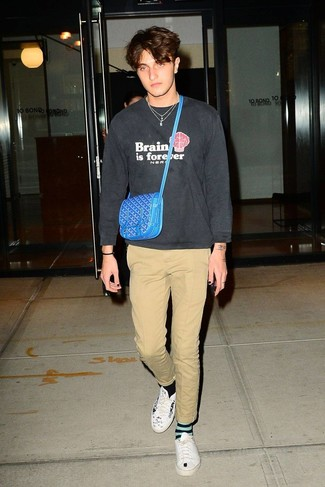 Wie kombinieren: dunkelgraues bedrucktes Sweatshirt, beige Chinohose, weiße und schwarze bedruckte Leder niedrige Sneakers, blaue Leder Bauchtasche