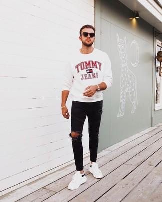 Wie kombinieren: weißes bedrucktes Sweatshirt, schwarze enge Jeans mit Destroyed-Effekten, weiße und schwarze Leder niedrige Sneakers, schwarze Sonnenbrille