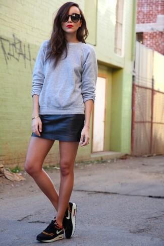 Wie kombinieren: graues Sweatshirt, schwarzer Leder Minirock, schwarze und weiße Sportschuhe, schwarze Sonnenbrille