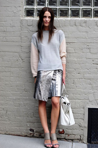 Wie kombinieren: graues Sweatshirt, silberner Leder Minirock, graue Leder Sandaletten, weiße Shopper Tasche aus Leder