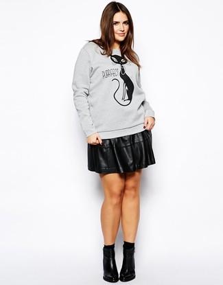 Wie kombinieren: graues bedrucktes Sweatshirt, schwarzer Skaterrock aus Leder, schwarze Leder Stiefeletten, schwarze Socken