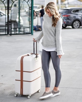 Dunkelgraue Leggings kombinieren: trends 2020: Um eine lockere und coole Silhouette zu formen, probieren Sie diese Kombi aus einem grauen Sweatshirt und dunkelgrauen Leggings. Dieses Outfit passt hervorragend zusammen mit grauen Slip-On Sneakers.