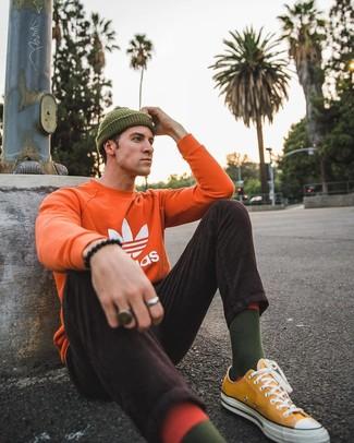 Wie kombinieren: orange bedrucktes Sweatshirt, dunkelbraune Cordjeans, senf Segeltuch niedrige Sneakers, olivgrüne Mütze