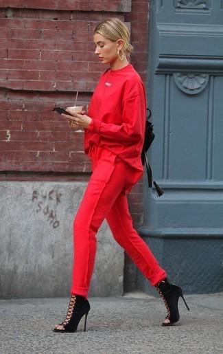 Wie kombinieren: rotes Sweatshirt, rote Jogginghose, schwarze Wildleder Stiefeletten mit Ausschnitten, schwarzer Leder Rucksack