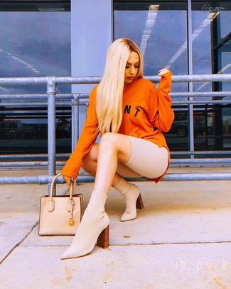 Wie kombinieren: orange bedrucktes Sweatshirt, hellbeige Radlerhose, hellbeige elastische Stiefeletten, hellbeige Shopper Tasche aus Leder
