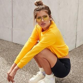 Wie kombinieren: gelbes Sweatshirt, schwarze Radlerhose, weiße hohe Sneakers aus Leder, weiße Socken