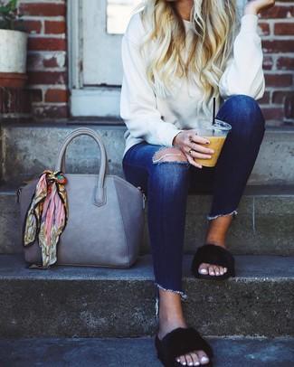 Wie kombinieren: weißes Sweatshirt, dunkelblaue enge Jeans mit Destroyed-Effekten, schwarze flache Sandalen aus Pelz, graue Shopper Tasche aus Leder