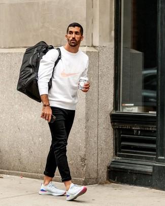 Wie kombinieren: weißes bedrucktes Sweatshirt, schwarze Jeans, weiße Sportschuhe, schwarze Segeltuch Sporttasche