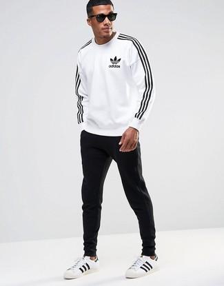 Wie kombinieren: weißes und schwarzes bedrucktes Sweatshirt, schwarze Jogginghose, weiße und schwarze Leder niedrige Sneakers, schwarze Sonnenbrille