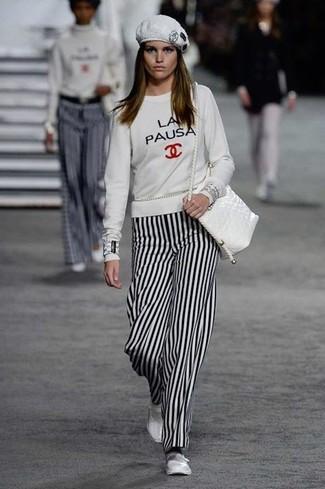 Wie kombinieren: weißes bedrucktes Sweatshirt, weiße und schwarze vertikal gestreifte weite Hose, weiße Leder Ballerinas, weiße Leder Umhängetasche
