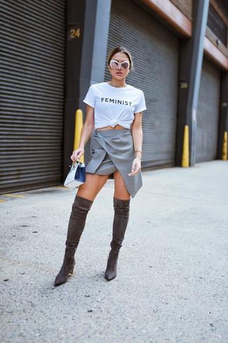 Wie kombinieren: weißes und schwarzes bedrucktes T-Shirt mit einem Rundhalsausschnitt, grauer A-Linienrock, dunkelbraune Overknee Stiefel aus Wildleder, weiße und schwarze Leder Clutch