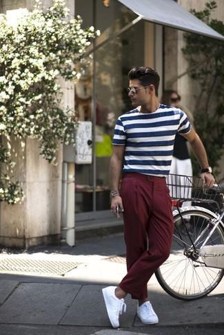 Wie kombinieren: dunkelblaues und weißes horizontal gestreiftes T-Shirt mit einem Rundhalsausschnitt, dunkelrote Anzughose, weiße niedrige Sneakers, dunkelbraune Lederuhr