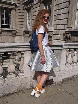 Wie kombinieren: weißes T-Shirt mit einem Rundhalsausschnitt, silberner ausgestellter Rock, weiße klobige Leder Sandaletten, dunkelblauer Jeans Rucksack