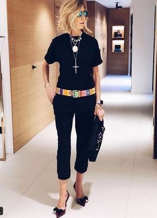 Wie kombinieren: schwarzes T-Shirt mit einem Rundhalsausschnitt, schwarze Caprihose, dunkelrote Leder Pumps, schwarze verzierte Wildleder Clutch