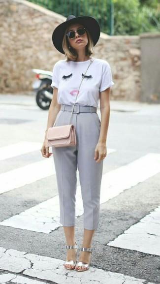 Wie kombinieren: weißes besticktes T-Shirt mit einem Rundhalsausschnitt, graue Caprihose, silberne Leder Sandaletten, rosa Leder Umhängetasche
