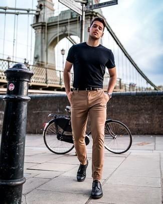 Smart-Casual Outfits Herren 2020: Die Paarung aus einem dunkelblauen T-Shirt mit einem Rundhalsausschnitt und einer beige Chinohose ist eine komfortable Wahl, um Besorgungen in der Stadt zu erledigen. Fühlen Sie sich mutig? Entscheiden Sie sich für schwarzen Leder Brogues.