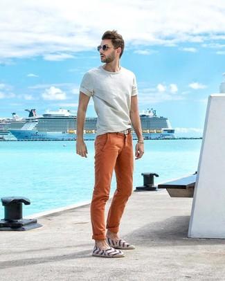 Wie kombinieren: weißes T-Shirt mit einem Rundhalsausschnitt, orange Chinohose, weiße horizontal gestreifte Segeltuch Espadrilles, weißer geflochtener Segeltuchgürtel