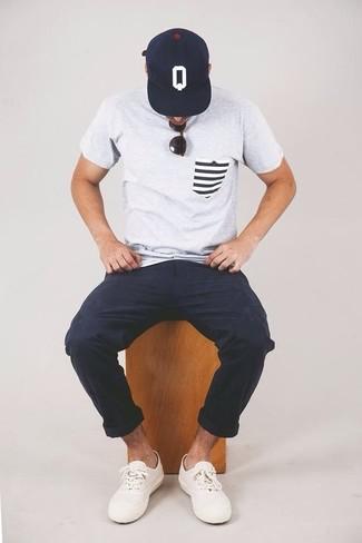 Wie kombinieren: graues T-Shirt mit einem Rundhalsausschnitt, dunkelblaue Chinohose, weiße niedrige Sneakers, dunkelblaue und weiße bedruckte Baseballkappe