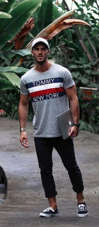 Wie kombinieren: graues bedrucktes T-Shirt mit einem Rundhalsausschnitt, schwarze Chinohose, schwarze und weiße Segeltuch niedrige Sneakers, weiße Baseballkappe