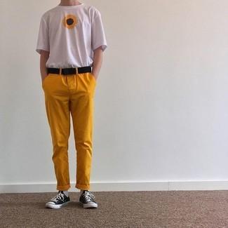 Wie kombinieren: weißes T-Shirt mit einem Rundhalsausschnitt mit Blumenmuster, senf Chinohose, schwarze und weiße Segeltuch niedrige Sneakers, schwarzer Segeltuchgürtel
